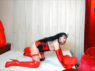 Posing On Mattress In Vinyl Long Boots And Corset
